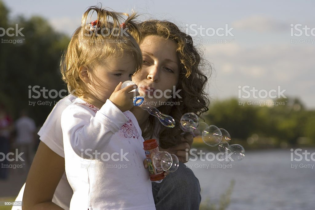 Little girl and her mom makes bubble royalty-free stock photo