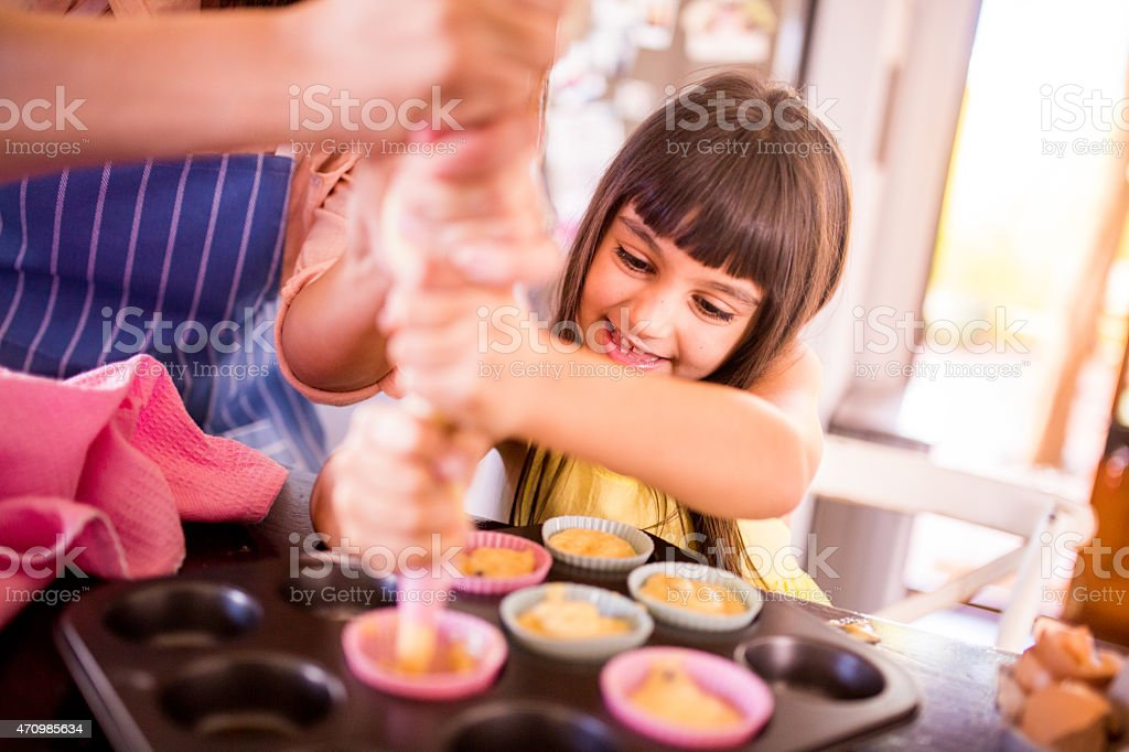 Little girl and her mom making cupcakes together stock photo