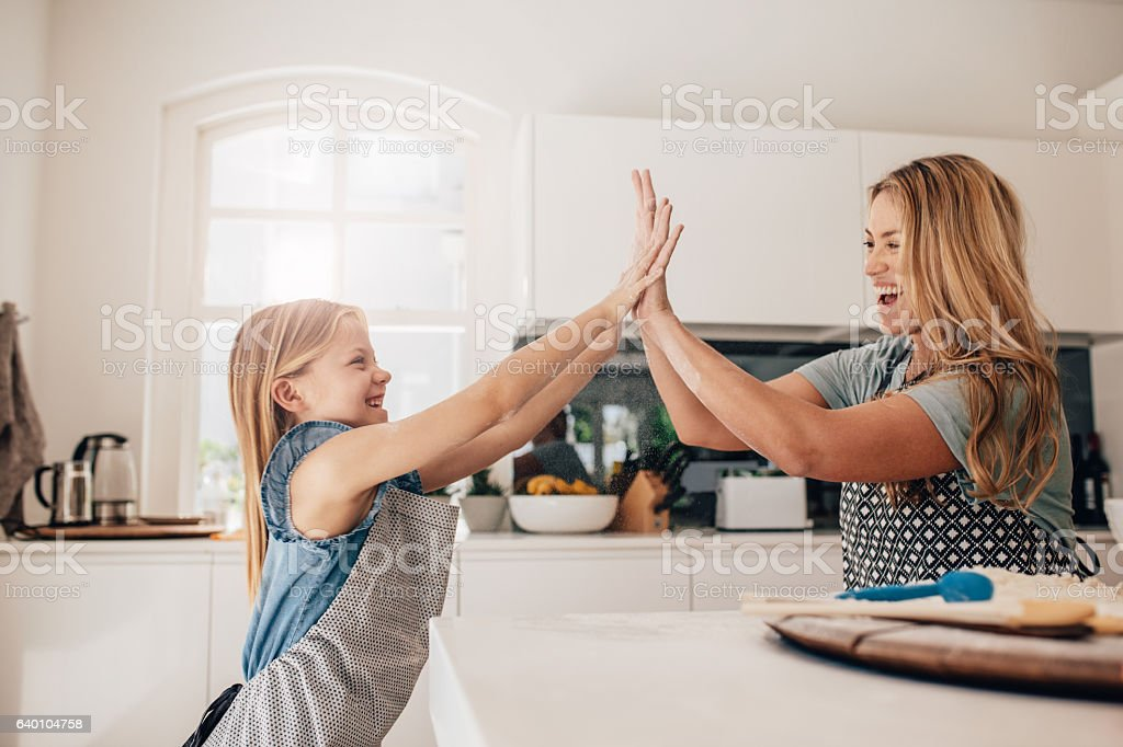 Little girl and her mother in kitchen giving high five stock photo