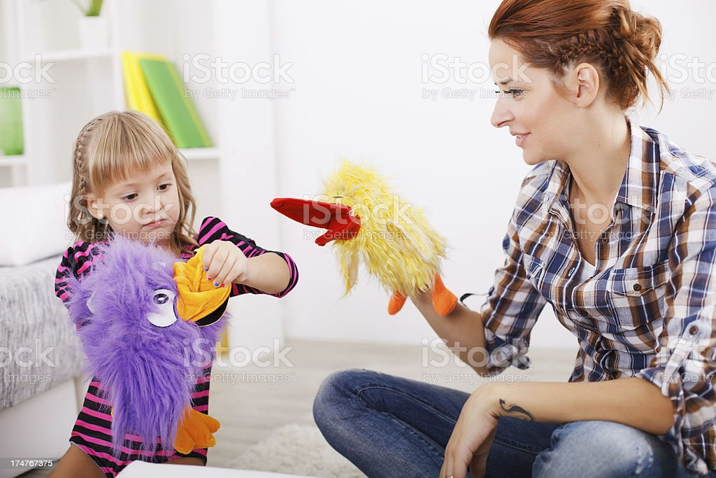 Little girl and her mother playing theatre. stock photo