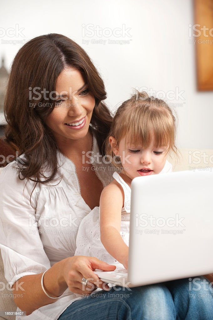 Little girl and her mother using a laptop royalty-free stock photo