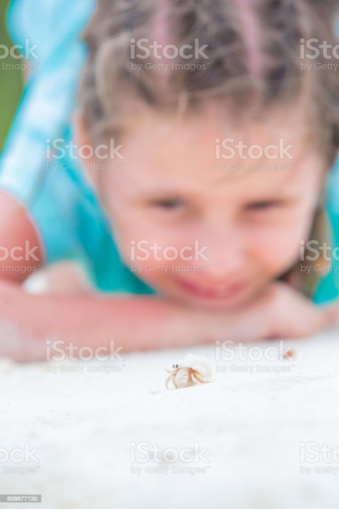 Little Girl And Hermit Crab On The Maldives Beach stock photo