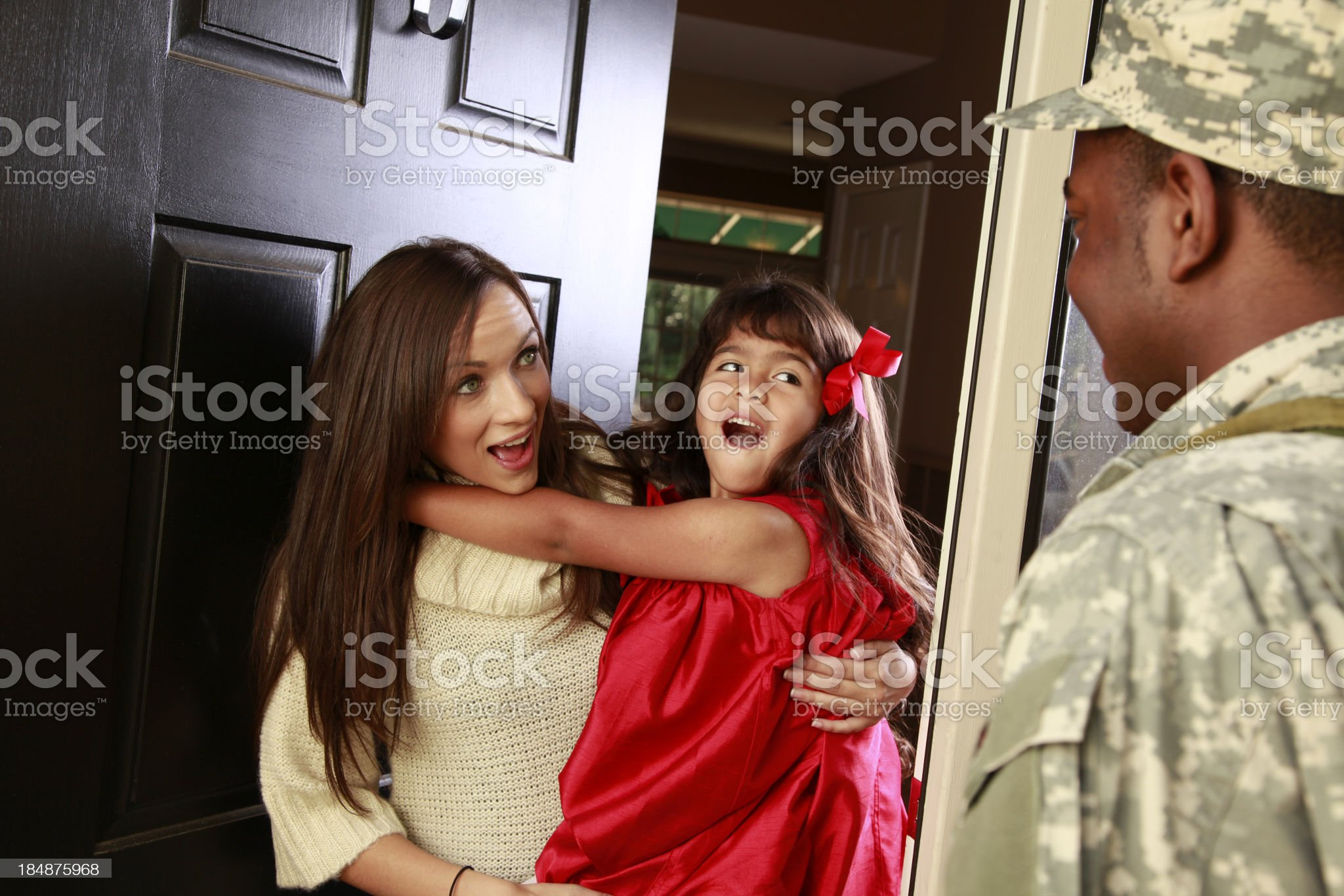 Little girl and mom welcome home military soldier father.  Excited. royalty-free stock photo