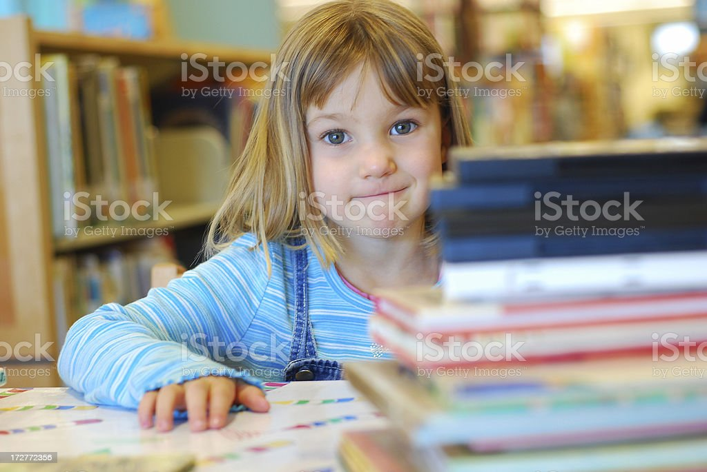 Little girl and piles of books in library royalty-free stock photo