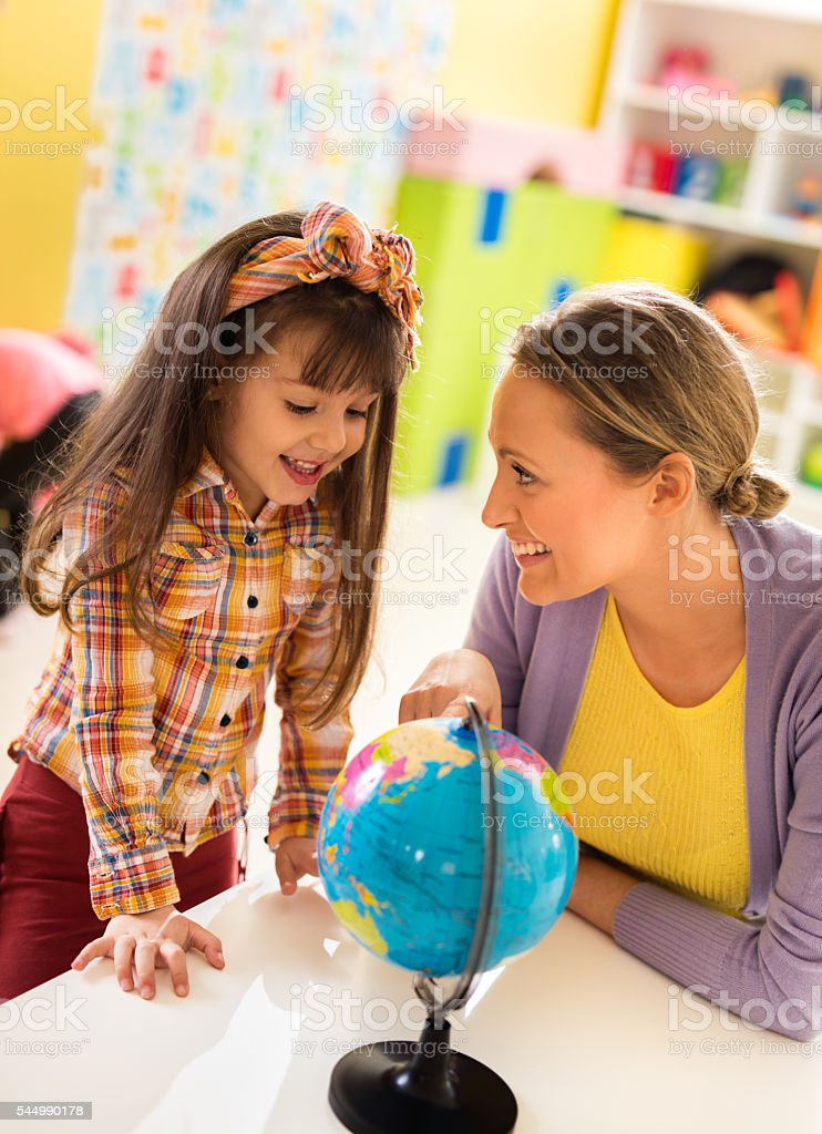 Little girl and preschool teacher studying world globe together. stock photo