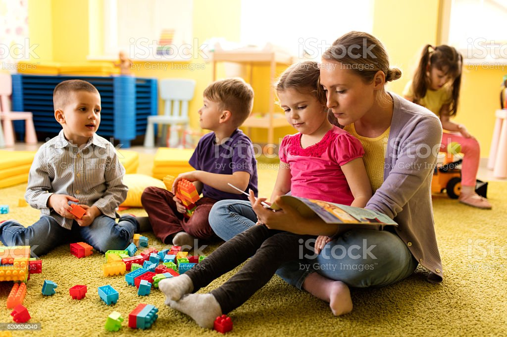 Little girl and teacher reading a book at preschool. stock photo