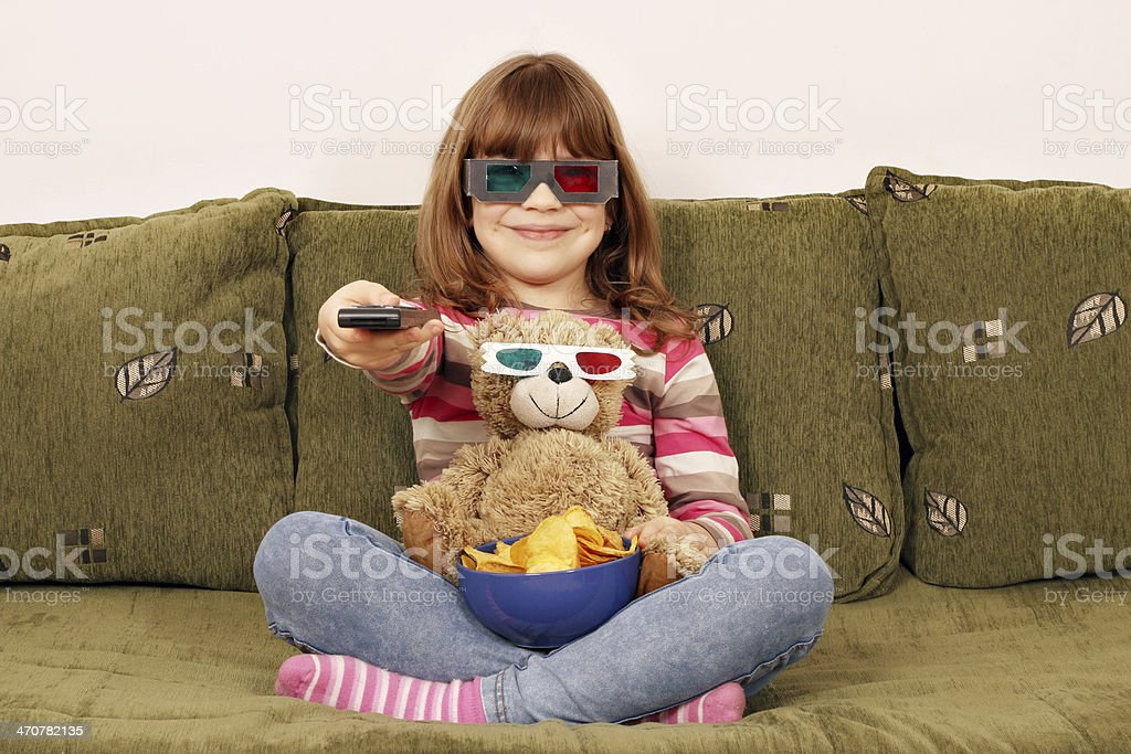 little girl and teddy bear with 3d glasses watching tv stock photo