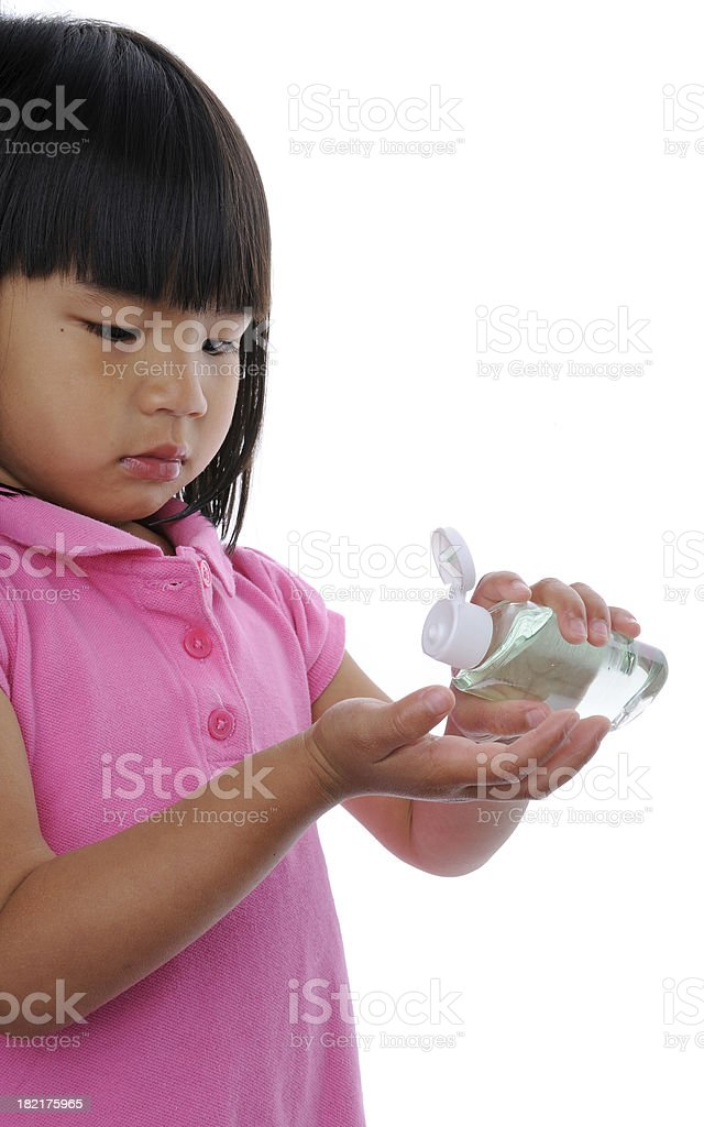 Little Girl Applying Hand Sanitizer stock photo