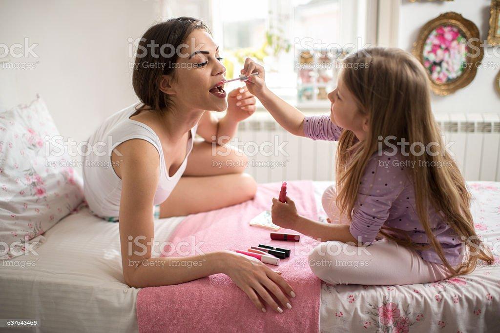 Little girl applying lip gloss on mother's lips in bedroom. stock photo