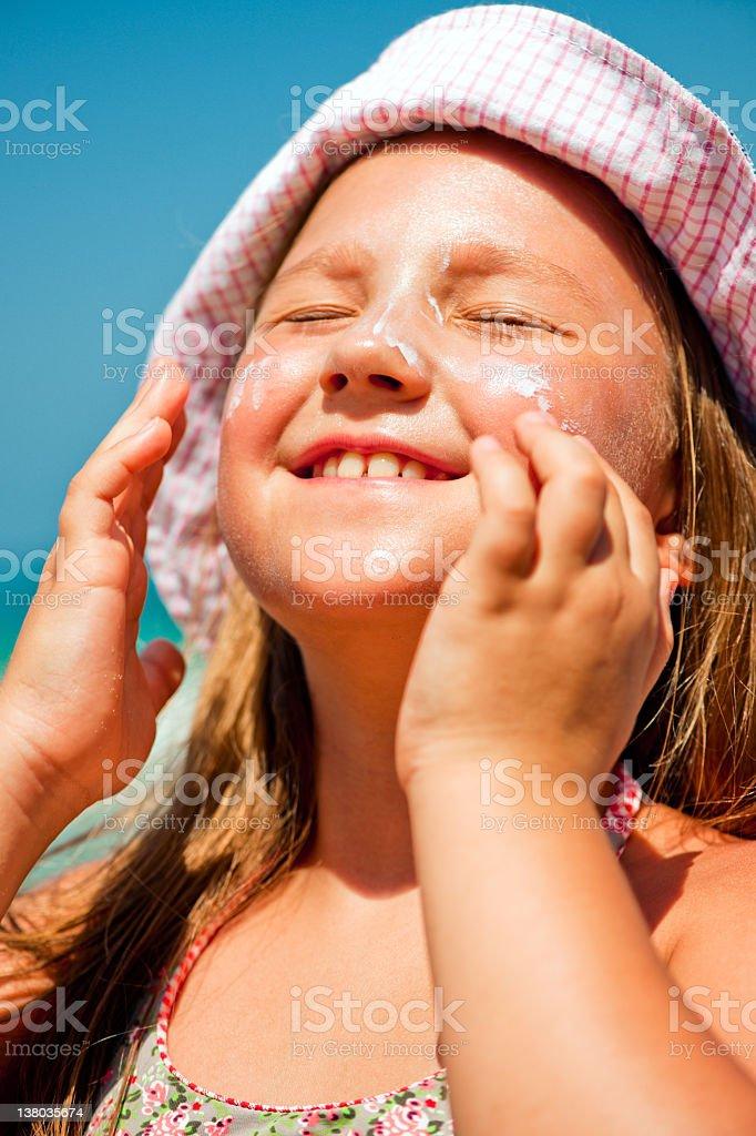 Little girl applying sun-protection lotion stock photo
