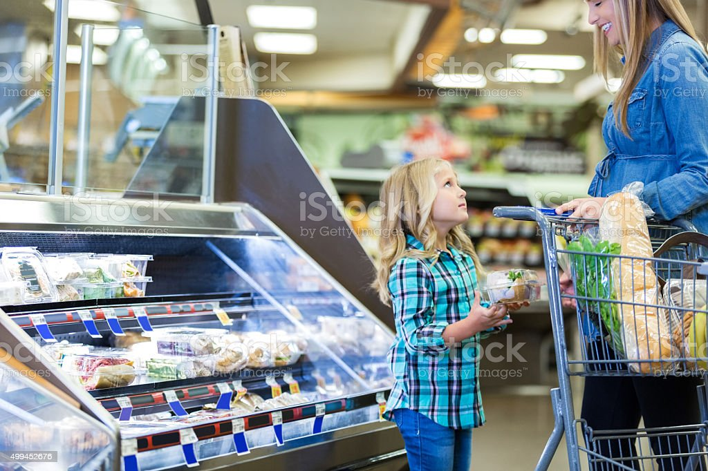 Little girl asking mom for something while grocery shopping stock photo