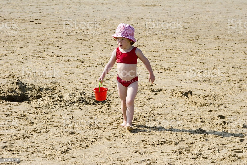 Little girl at beach carrying bucket with sand royalty-free stock photo