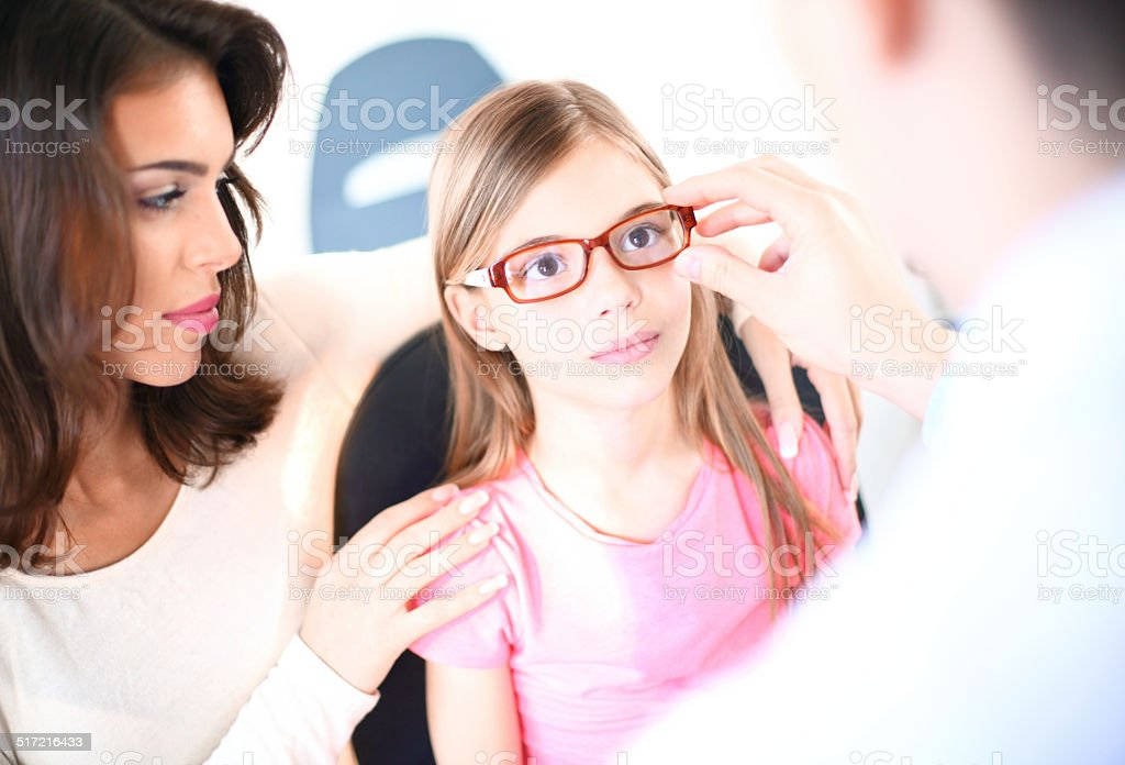 Little girl at optician. stock photo