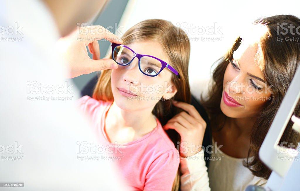 Little girl at optician's office. stock photo