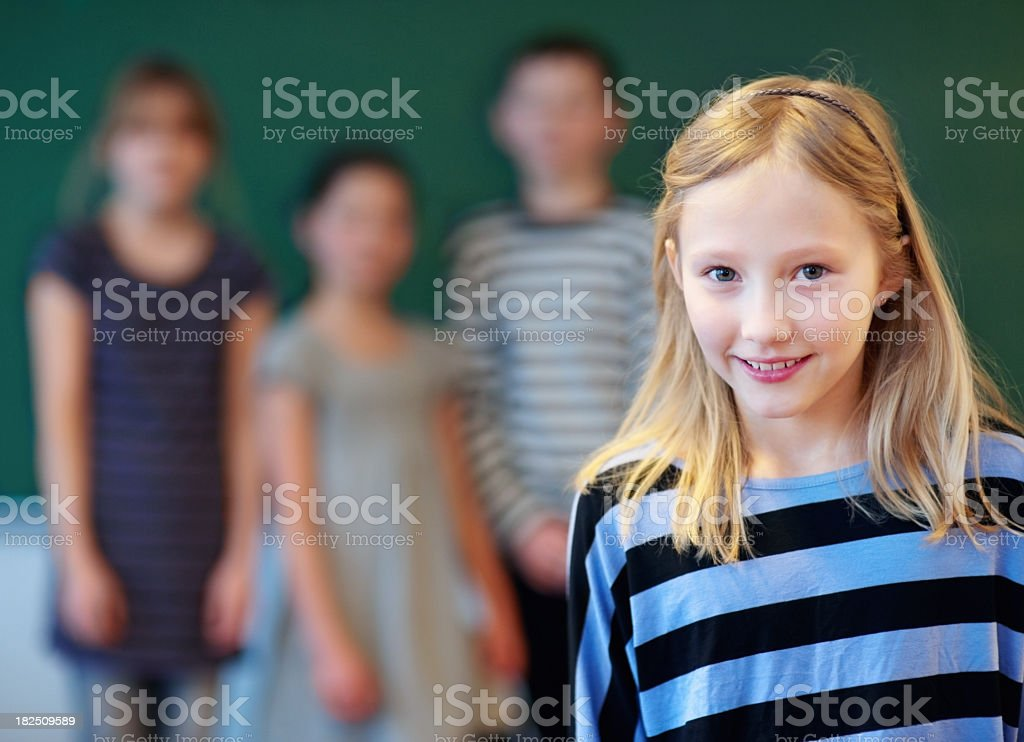 Little girl at school with her classmates in the background royalty-free stock photo