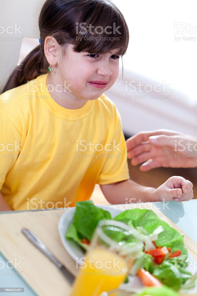 Little girl at table crying, doesn't want to eat vegetables royalty-free stock photo