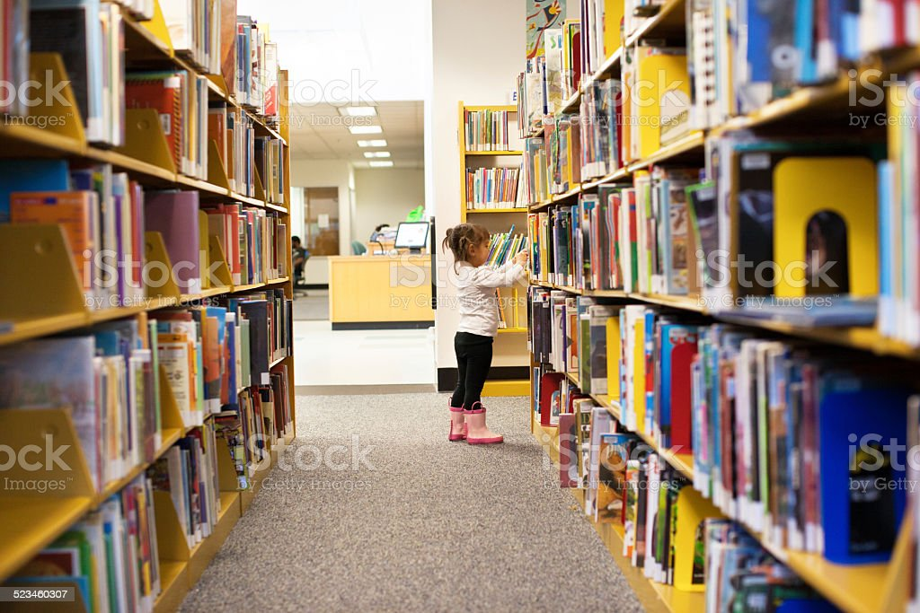 Little Girl At The Library Picking a Book stock photo