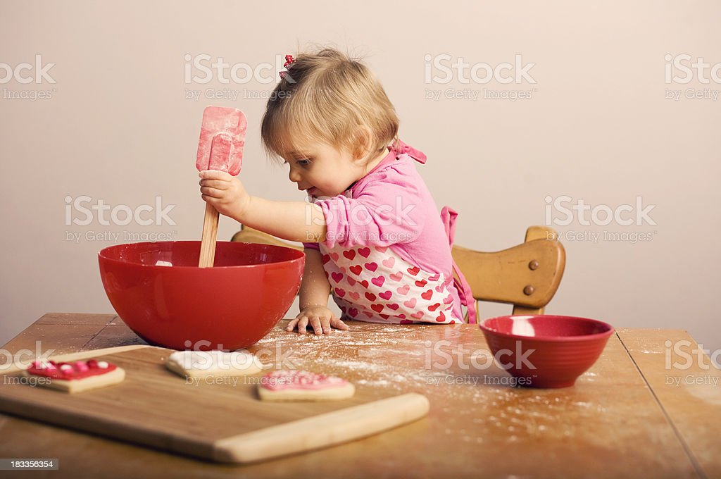 Little Girl Baking Valentine's Cookies in the Kitchen stock photo