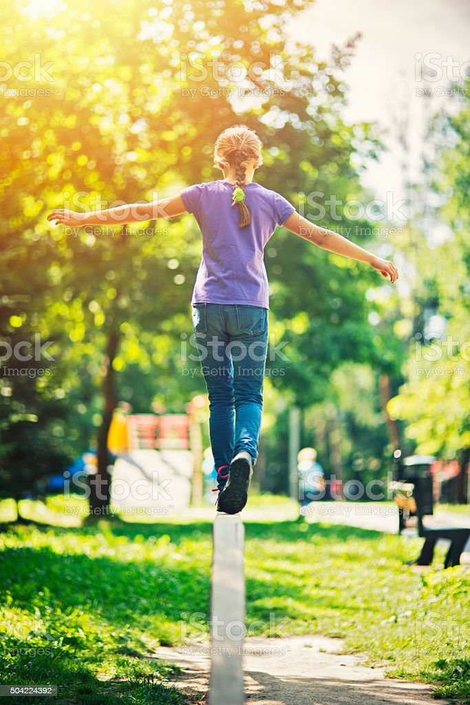 Little girl balancing on a balance beam in sunny park stock photo