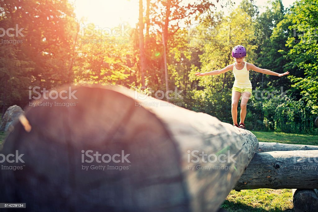 Little girl balancing on a trunk in adventure park stock photo