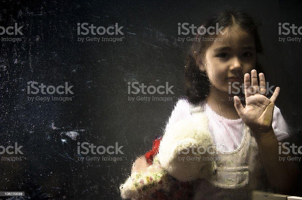 Little Girl Behind Wet Window Holding Teddy Bear stock photo
