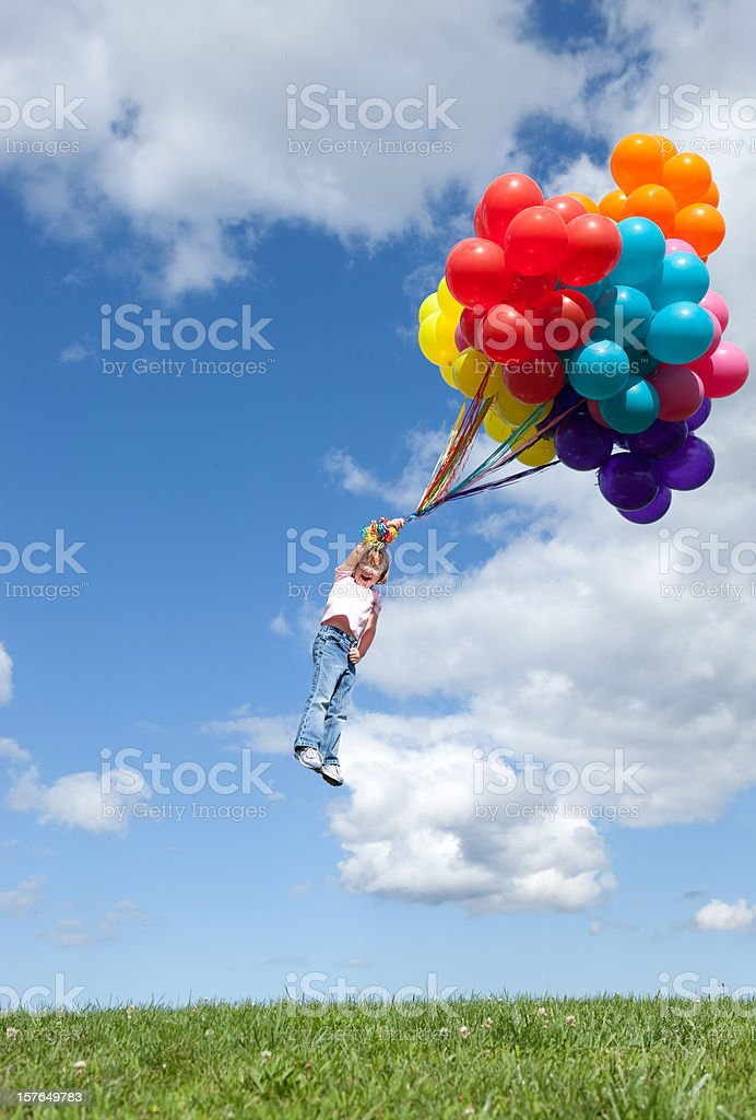 Little Girl Being Blown Away While Holding Bunch of Balloons royalty-free stock photo