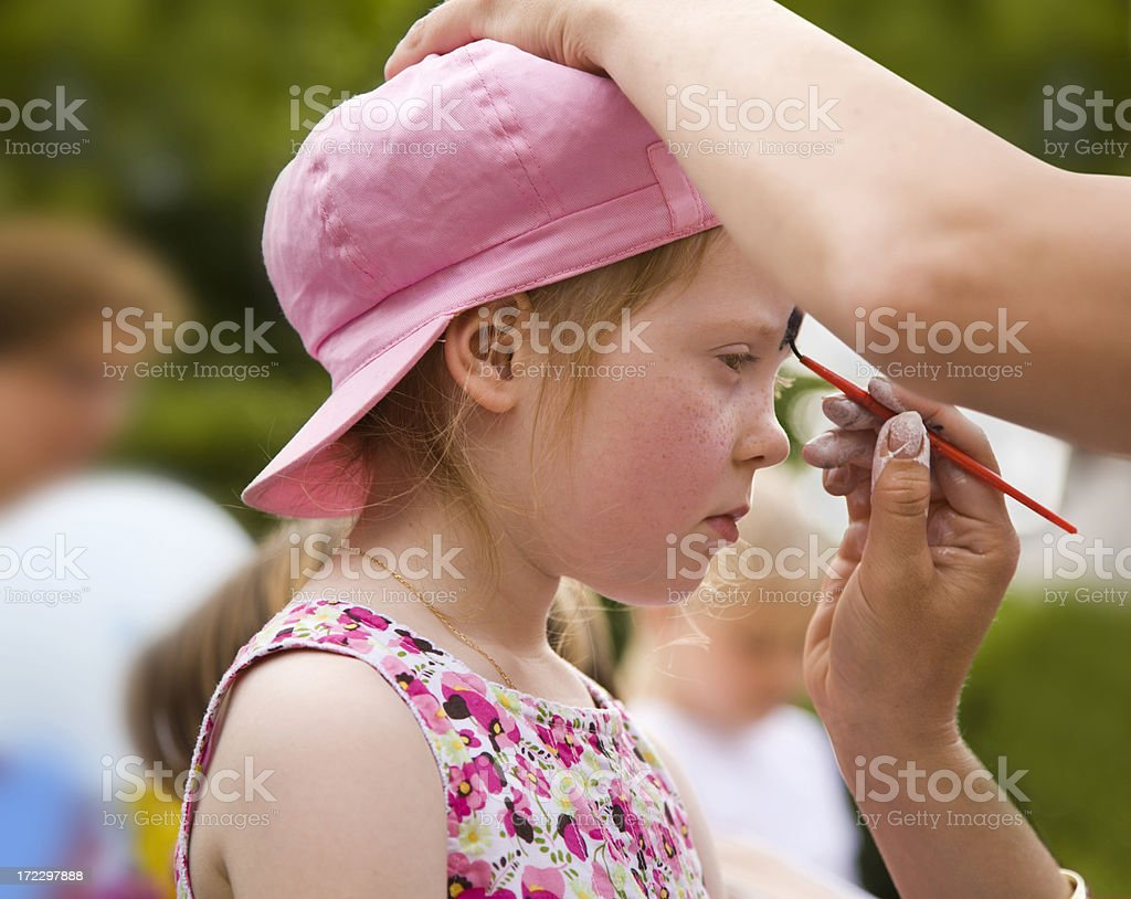 Little girl being body-painted royalty-free stock photo