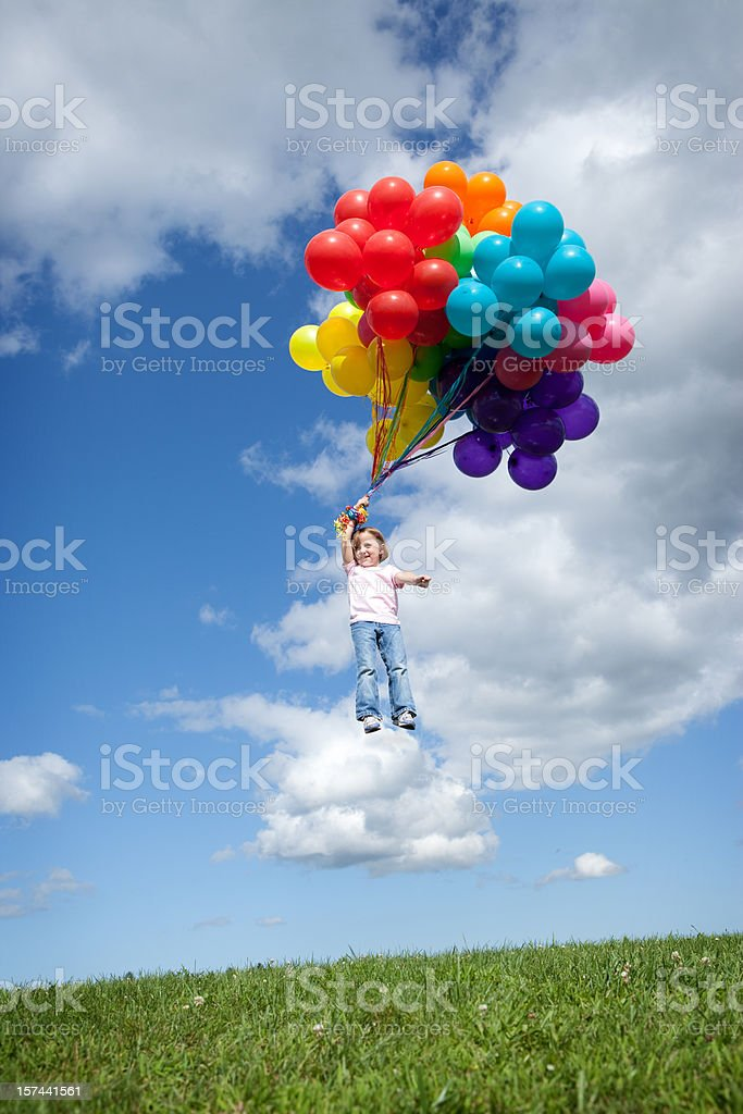Little Girl Being Carried Away by Balloons stock photo
