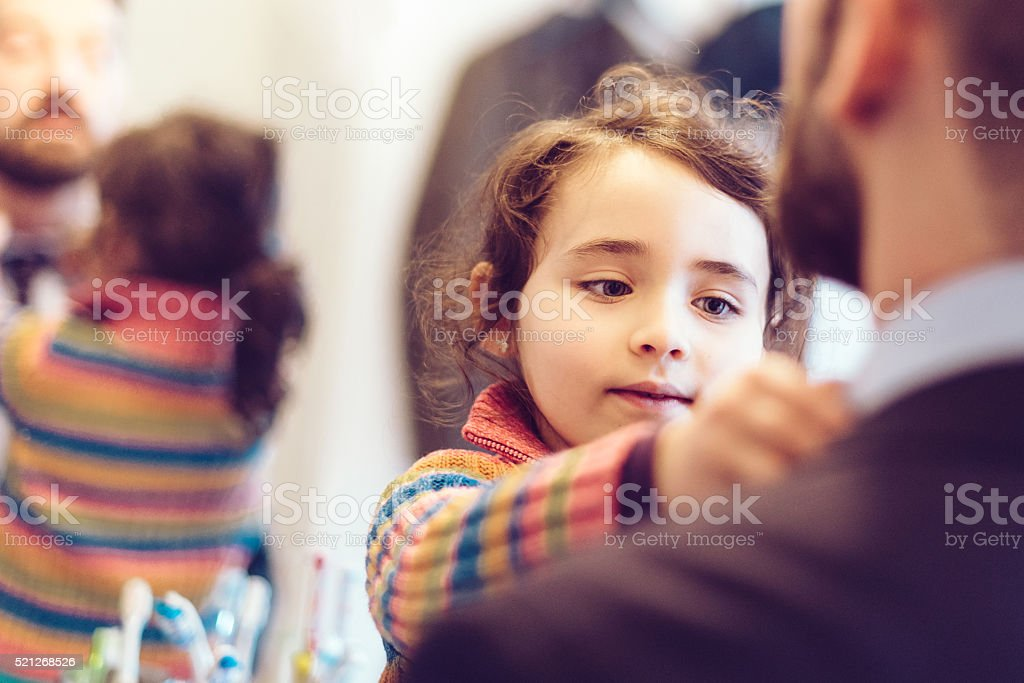 little girl binding tie to father in business outfit stock photo