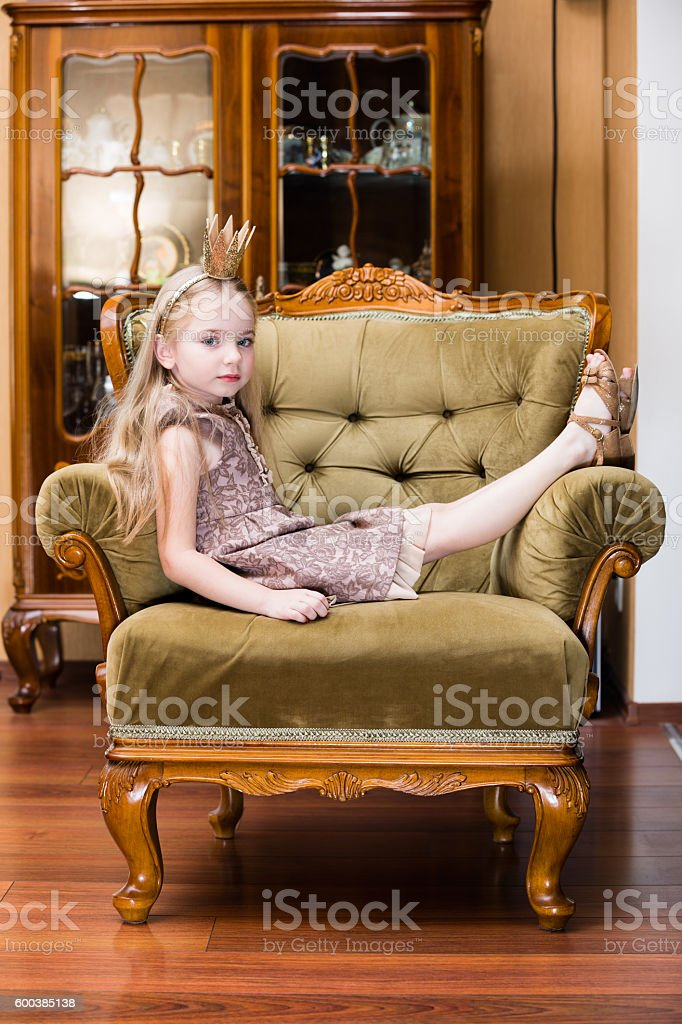 little girl blond hair wearing crown standing at the chair stock photo