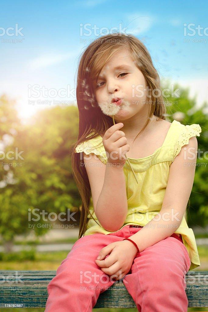 Petite fille de soufflage des graines de pissenlit photo libre de droits