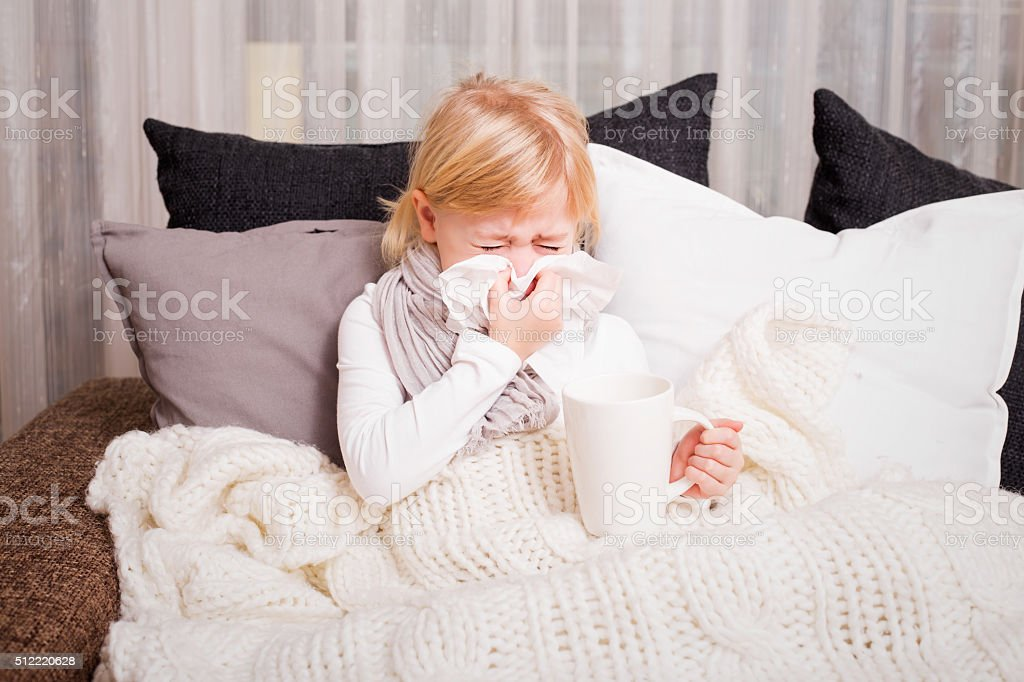 Little girl blowing her nose in napkin stock photo