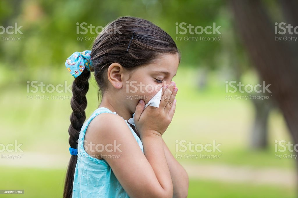Little girl blowing his nose stock photo