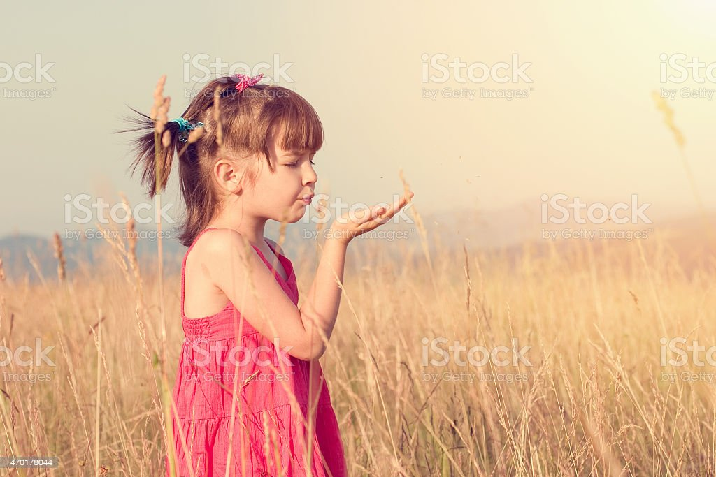 Little girl blowing seeds from her palm stock photo