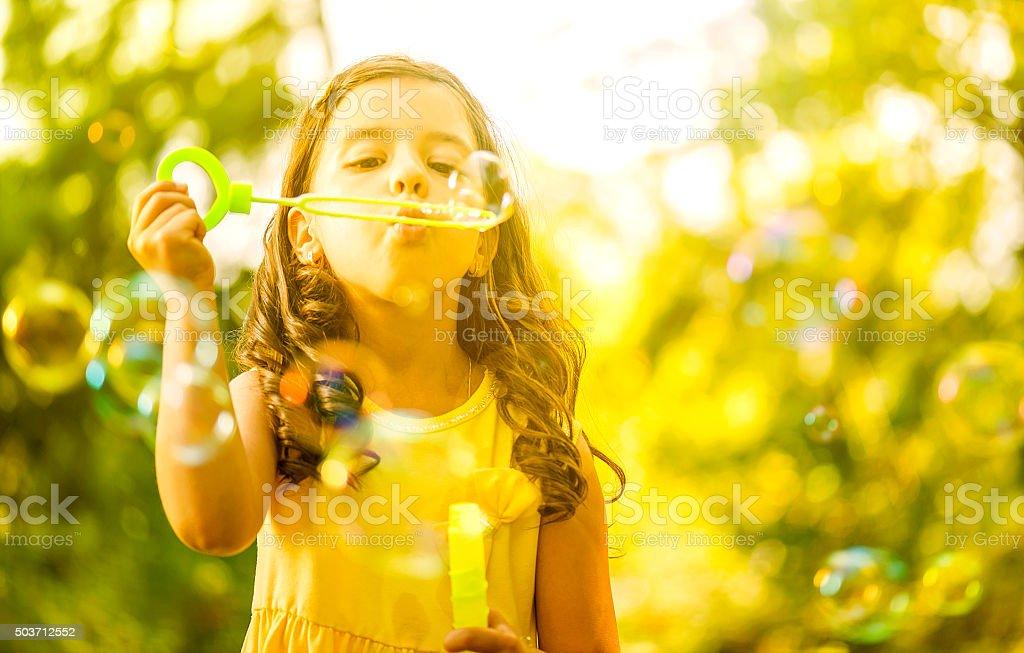 Little girl blowing soap bubble stock photo