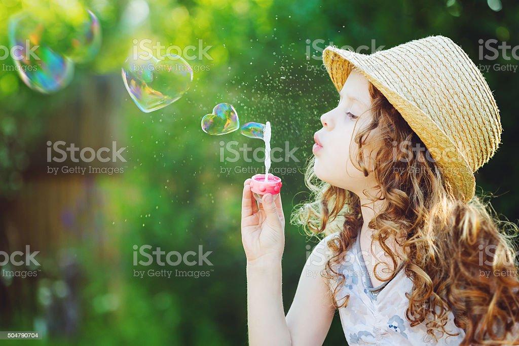 Little girl blowing soap bubbles in a heart shape. stock photo
