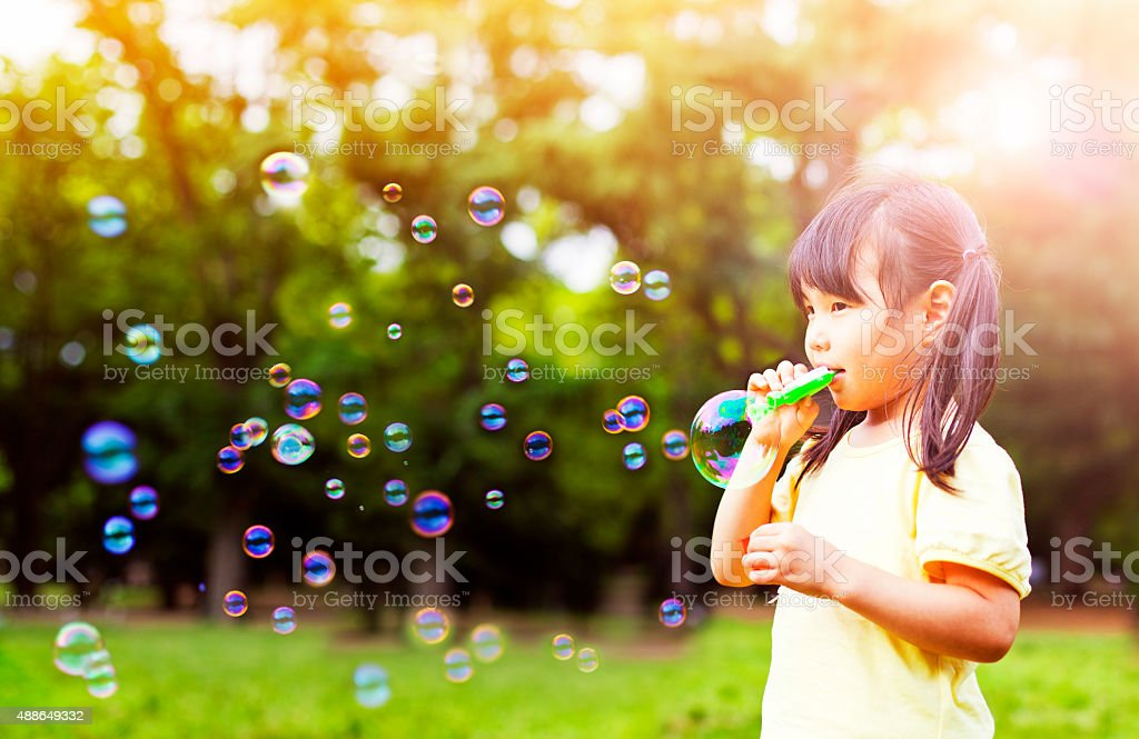 Little girl blowing soap bubbles stock photo