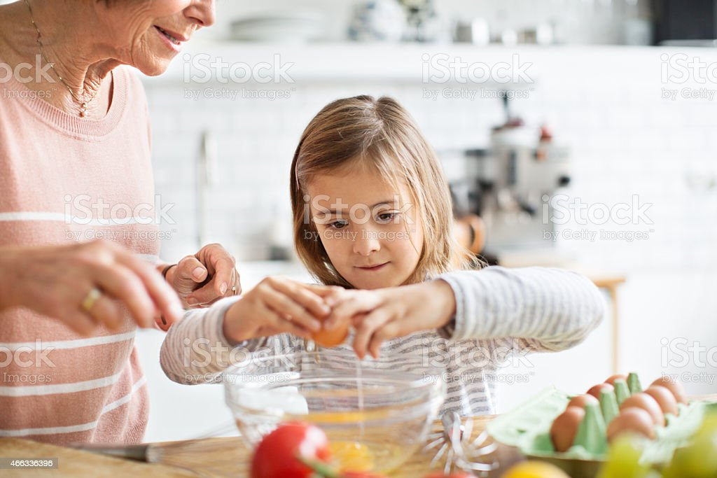 Little girl breaking an egg in kitchen stock photo