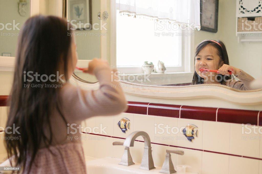Little girl brushing her teeth in bathroom stock photo