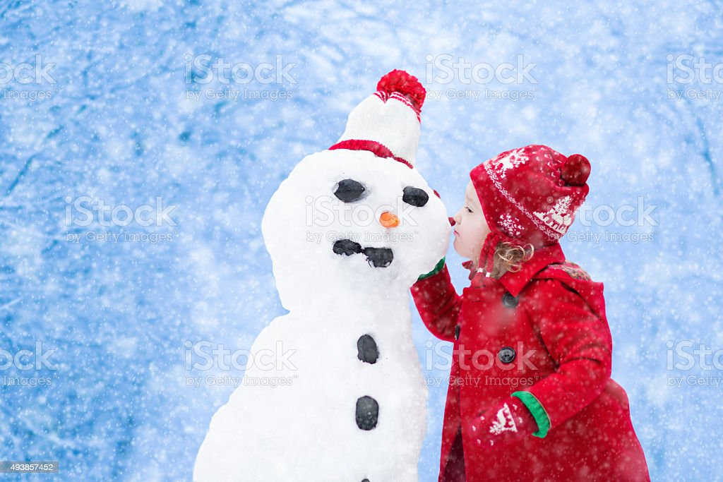 Little girl building a snow man in winter stock photo