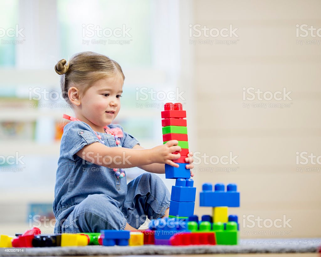 Little Girl Building Lego Towers stock photo