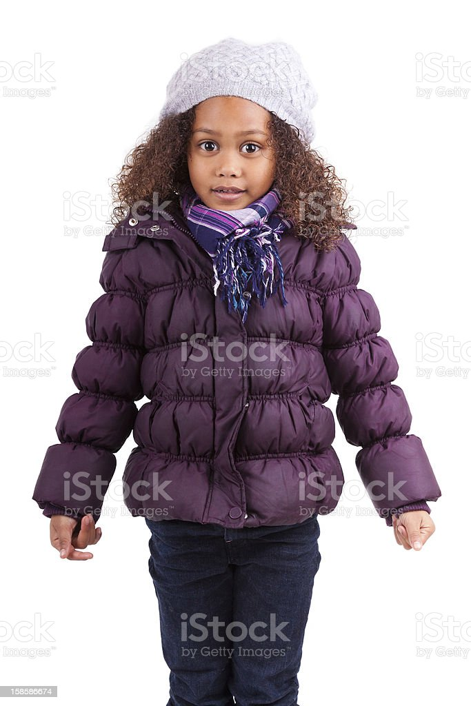 Little girl bundled up in a hat and purple coat on white stock photo