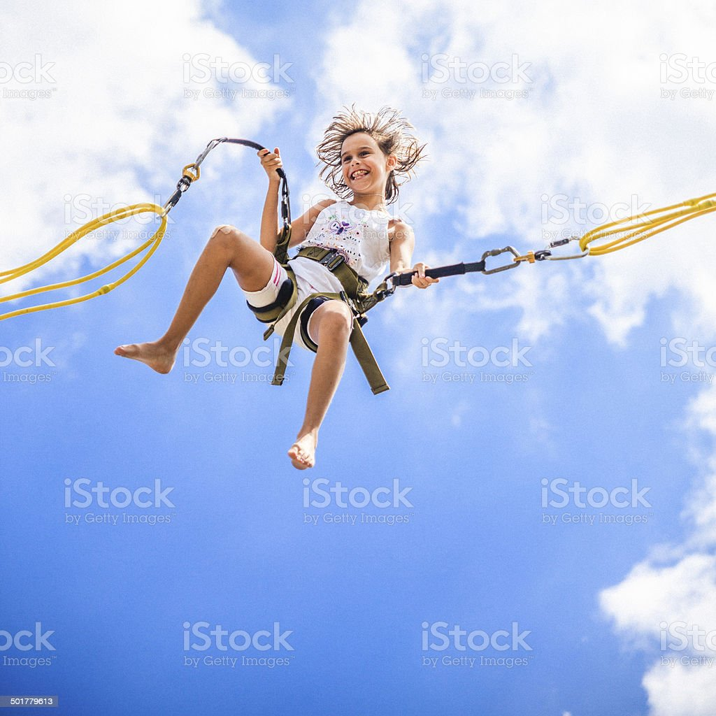 Little girl bungee jumping at trampoline stock photo