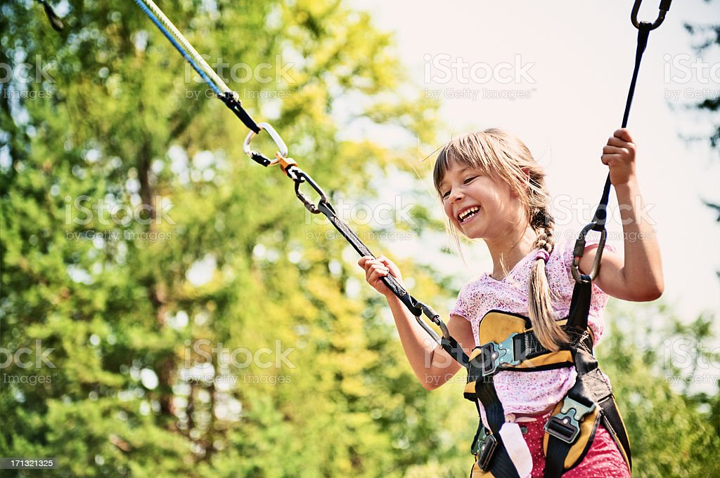 Little girl bungee jumping on trampoline stock photo