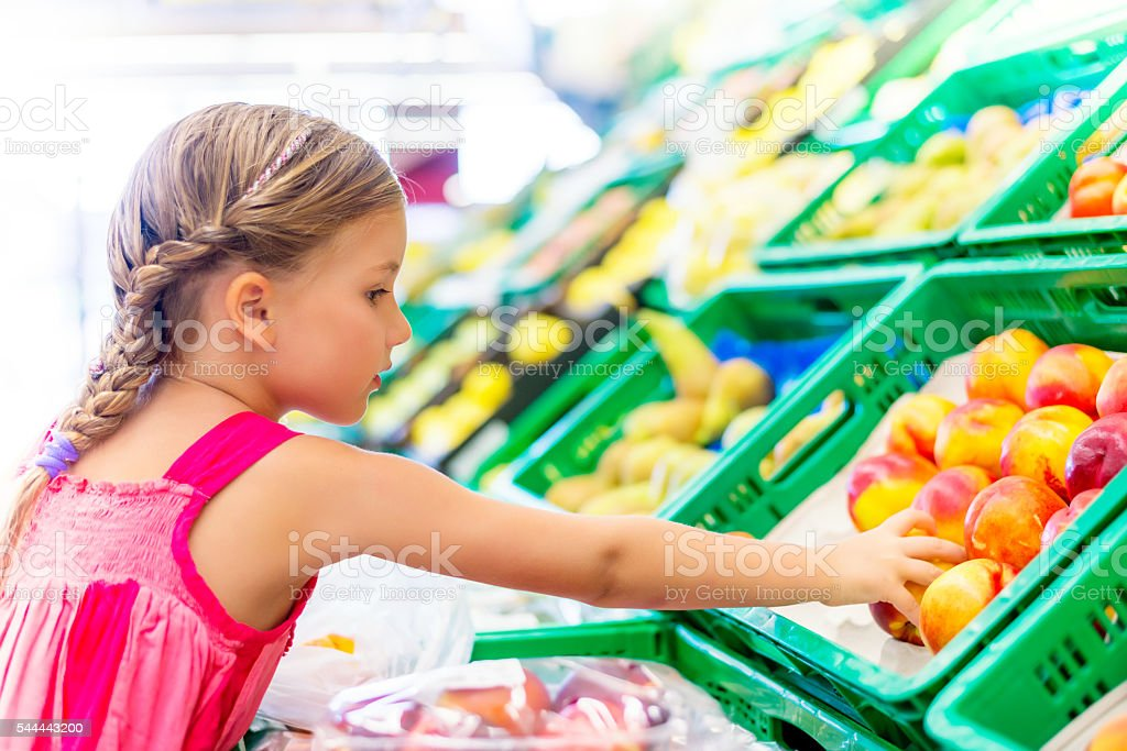 little girl buying healthy foods stock photo