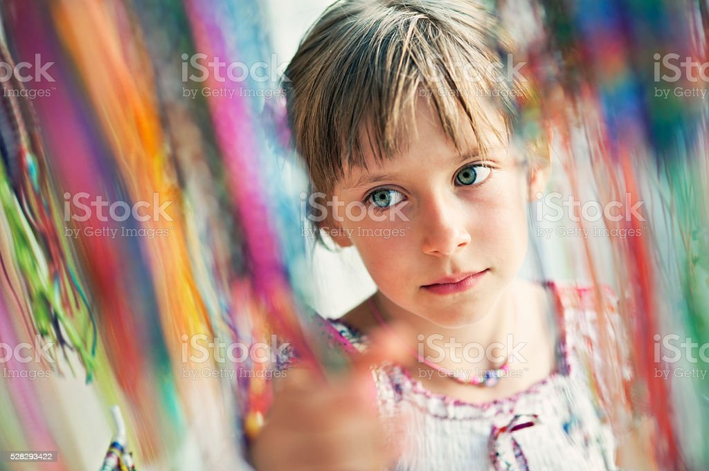 Little girl buying vacation souvenir necklace stock photo
