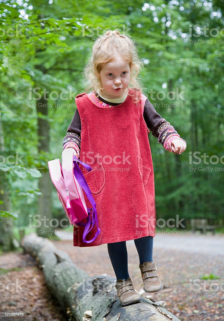 Little girl, carefully climbing a fallen tree in the forest royalty-free stock photo
