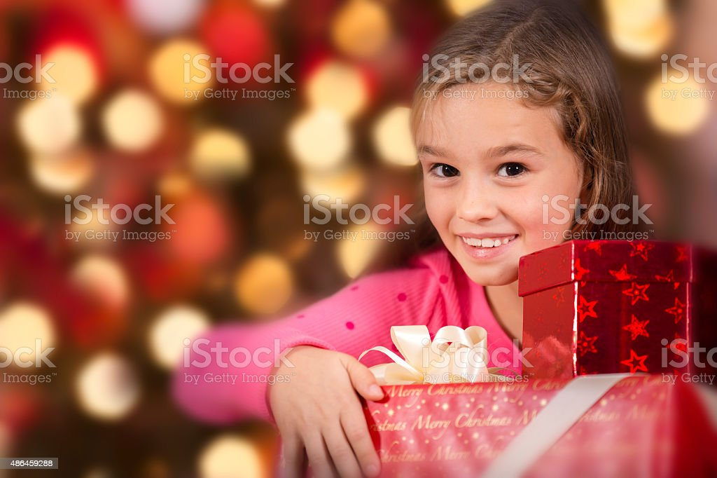 Little girl carries stack of Christmas presents. Tree background. stock photo