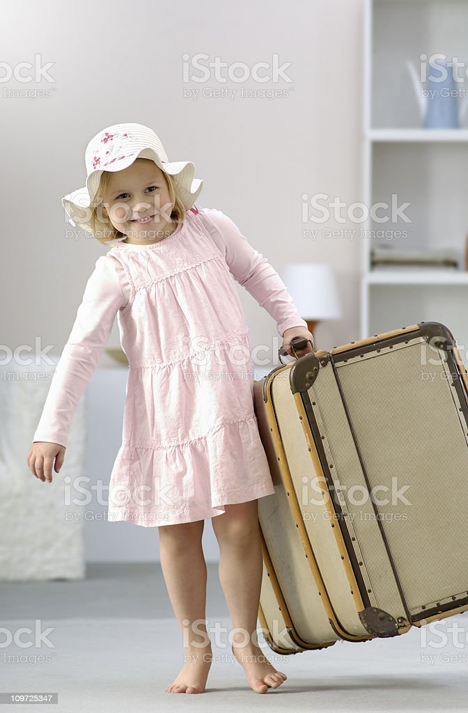 Little Girl Carrying Large Classic Suitcase stock photo