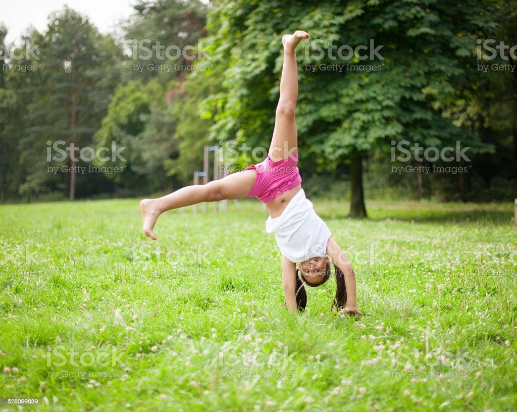 Little girl cartwheeling in meadow stock photo